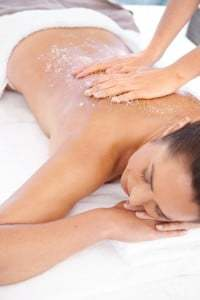 A woman relaxing while enjoying an exfoliating beauty treatment at a spa